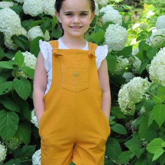Child wearing the Baby/Child Tipa Dungarees sewing pattern by Below the Kowhai. A sleeveless dress pattern made in light to medium weight cotton, chambray, linen, or medium to heavy weight denim, drill or twill fabrics, featuring cross over back straps and side and front pockets.