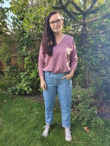 woman wearing light blue jeans and mauve coloured v-neck top, standing in the garden.
