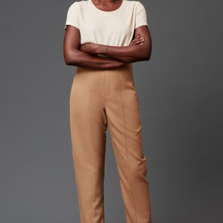 Woman wearing the Acajou Pants sewing pattern by Deer and Doe. A trouser pattern made in cotton, linen or wool fabric featuring a high waist, tapered legs, front seams and elasticated back waistband.