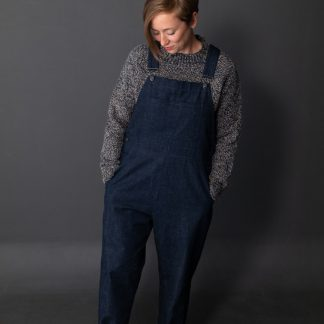 Woman wearing the Harlene Dungarees sewing pattern by Merchant and Mills. A dungaree pattern made in denim, cotton canvas, corduroy, or linen fabric featuring five pockets, top stitching and an easy fit.