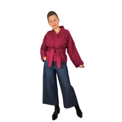 Woman wearing The Overlap Jacket sewing pattern by Dhurata Davies Patterns. A wrap jacket pattern made in lightweight breezy linen to cosy wool fabric, featuring a belt and loops, patch pockets and hip length.
