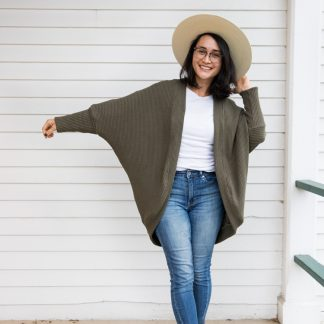 Woman wearing the Carrie Cardigan sewing pattern by Delia Creates. A cardigan pattern made in knit or light weight woven fabrics, featuring a relaxed fit, split front and with dolman style sleeves.