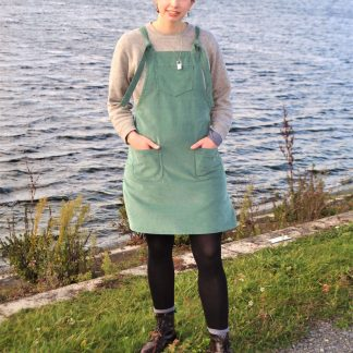 Woman wearing the Dunga Dress sewing pattern from Stitched in Wonderland on The Fold Line. A dungaree dress pattern made in cotton poplin, denim, corduroy, linen, canvas or wool fabrics, featuring patch pockets, chest pocket, adjustable shoulder straps, and above knee length hem.