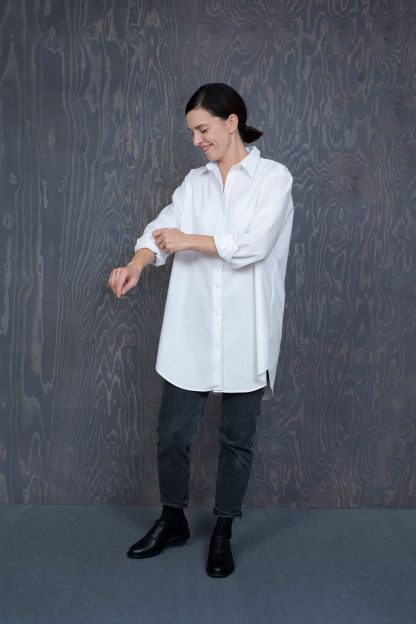 Woman wearing the Oversized Shirt sewing pattern by The assembly Line. A shirt pattern made in cotton, linen, lawn or silk fabric featuring a classic style with an oversized fit, side seam pockets, front button closure, rear box pleat and traditional shirt collar.