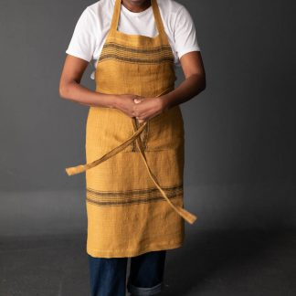 Woman wearing the Unisex Workday Apron sewing pattern by Merchant and Mills. A long length apron pattern made in cotton canvas, cotton twill, medium to heavy weight linen or oilskin fabric featuring three pockets, waist ties and adjustable neck strap.