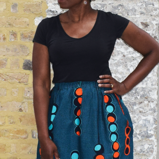 Woman wearing the Althea A-Line Skirt sewing pattern by Dovetailed. A skirt pattern made in wax print, cottons, gauze, linen, silks, chambray, georgette or poplin fabrics, featuring an A-line silhouette, elasticated waistband and side pockets.