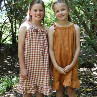 Children wearing the Baby/Child Kororā Dress sewing pattern by Below the Kowhai. A sleeveless dress pattern made in light to medium weight cotton, chambray, lawn, linen, rayon, viscose or voile fabrics, featuring a halter neck and shoulder ties, plus a ruffle hem.