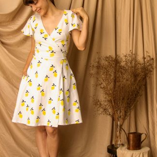 Woman wearing the Mathilde Wrap Dress sewing pattern from Untitled Thoughts on The Fold Line. A wrap dress pattern made in knit fabrics, featuring a back waist tie, V-neck, short flutter sleeves, French darts, in-seam pockets and knee length finish.