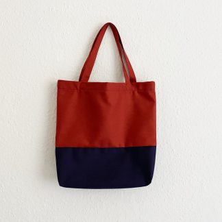 Picture showing the Ava Tote Bag sewing pattern from Tammy Handmade on The Fold Line. A tote bag pattern made in canvas, linen or upholstery weight fabrics, featuring a colour blocking effect and looped handles.