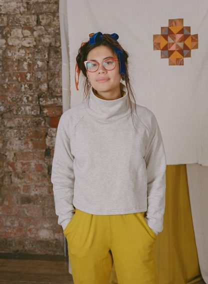 Woman wearing the Zahra Jumper sewing pattern from Made My Wardrobe on The Fold Line. A jumper pattern made in heavy weight knit fabrics, featuring a loose fit, raglan sleeves, cropped length and a high funnel neck.