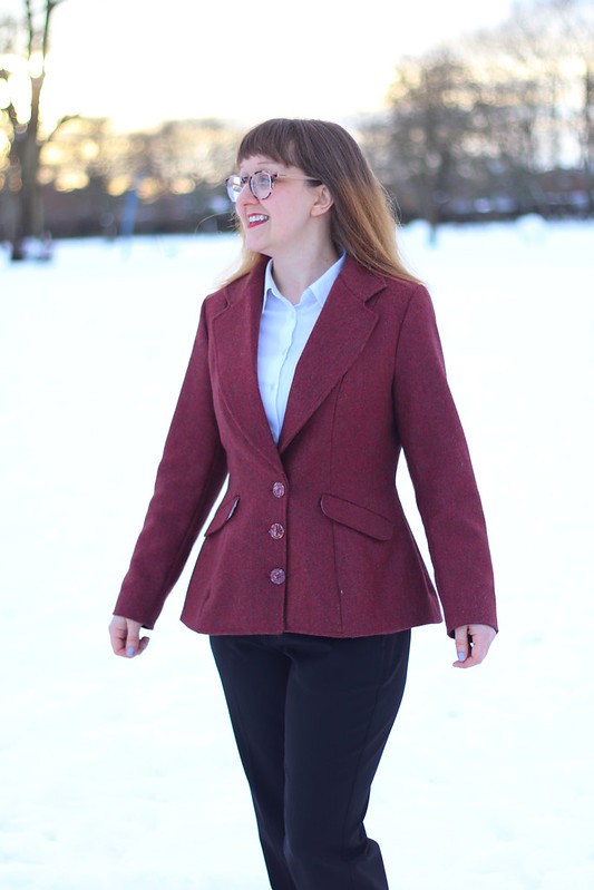 Woman wearing the Barberry Jacket sewing pattern by Charlotte Emma Patterns. A jacket pattern made in suitings, wool, tweed, brocade or cotton fabrics, featuring a shaped slim-fit with a cinched waist, three button closure, pockets and exaggerated hemline.