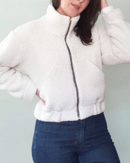 Women wearing the Cozi Jacket sewing pattern from Pattern Scout on The Fold Line. A jacket pattern made in knit or woven fabrics, featuring a zip front closure, oversized cropped fit, dropped shoulder and large patch front pockets, high neck and elasticated waist band and cuffs.