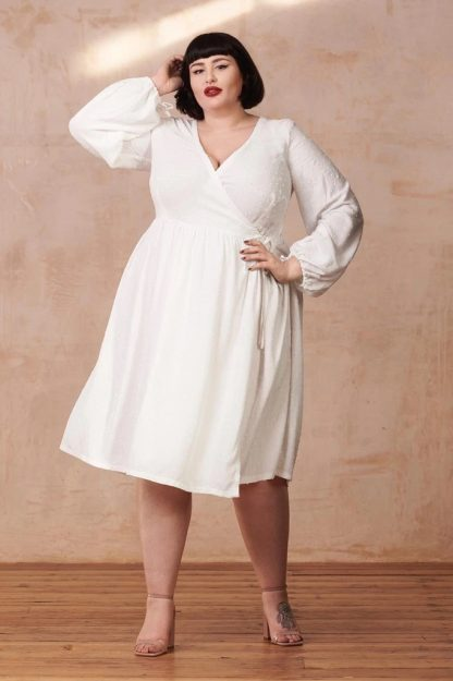Woman wearing the Hannah Dress sewing pattern from By Hand London. A wrap dress pattern made in cottons, linens or viscose fabrics, featuring a scoop wrap neckline, gently gathered skirt and long sleeves.