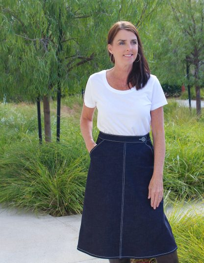 Woman wearing the No-Zip Skirt sewing pattern by Blue Dot Patterns. An A-line skirt pattern made in denim, twill, corduroy, suitings, sateen, poplin or linen fabrics, featuring a fitted waist, slash pockets, button and hook and eye closure.