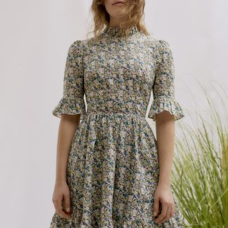 Woman wearing the Alexa Frill Dress sewing pattern by Liberty Sewing Patterns. A dress pattern made in cotton, satin or poplin fabrics, featuring elbow length sleeves with frill, stand frill collar, fitted bodice, flared skirt with tiered frill and back zipper closure.