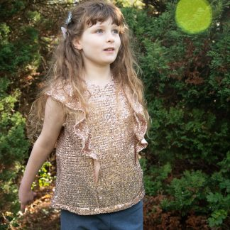 Child wearing the Baby/Child/Teen Alice Top sewing pattern by Bobbins and Buttons. A sleeveless, top pattern made in cottons, double gauze or linen fabrics, featuring a deep ruffle that runs over the shoulder and keyhole back opening.