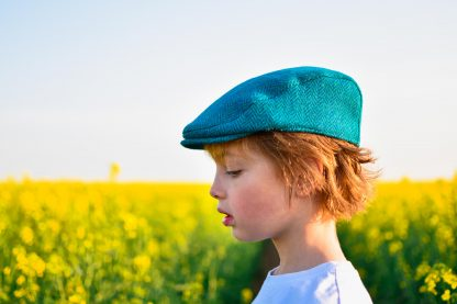 Child wearing the Baby/Child/Adult Fell and Dale Flat Cap sewing pattern by Wavers and Wild. A cap pattern made in wool tweed, wool blends, corduroy, denim or heavier linen fabrics, featuring optional elastic at the back and a brim or peak.