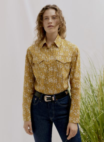 Woman wearing the Unisex Camargue Cowboy Shirt sewing pattern by Liberty Sewing Patterns. A shirt pattern made in cotton, or chambray fabrics, featuring a classic shirt collar, long sleeves with button cuffs, patch chest pockets and button front closure.