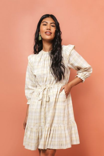 Woman wearing the Davenport Dress sewing pattern by Friday Pattern Company. A dress pattern made in cotton lawn or linen fabrics, featuring roomy pockets, full sleeves with an elastic ruffle hem, shoulder flutter detail, a drawstring waist and tiered hem.