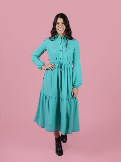 Woman wearing the Lyra Shirt Dress sewing pattern by Tilly and the Buttons. A dress pattern made in light to medium weight woven fabrics, featuring a button front opening, side seam pockets, long billowy sleeves with elasticated cuffs, side seam pockets and gathered skirt with a trendy tier.
