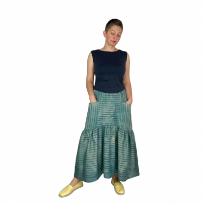 Woman wearing the Olive Skirt sewing pattern by Dhurata Davies Patterns. A tiered skirt pattern made in viscose, tencel, rayon, silk, crepe and some linen fabrics, featuring pockets, elasticated waist with minimal gathers and a dipped hem.