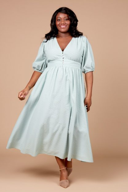 Woman wearing the Orchidée Dress sewing pattern by Deer and Doe. A dress pattern made in batiste, cotton voile, swiss dots or eyelet fabrics, featuring a deep V-neck, bridal buttons, zipper closure, elbow length puff sleeves, full skirt and deep waistband.