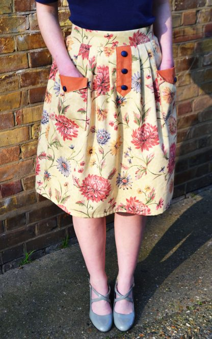 Woman wearing the Pocketful Skirt sewing pattern by Stitched in Wonderland. A pleated skirt pattern made in light to medium weight woven fabrics, featuring a high waist, front patch pockets and a false button placket on the front.