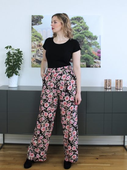 Woman wearing the Tyra Trousers sewing pattern by Ploen Patterns. A palazzo trouser pattern made in light to medium weight wovens such as viscose, tencel, polyester or crepe fabrics, featuring a high waist, wide leg, front pockets and wide elasticated waistband.