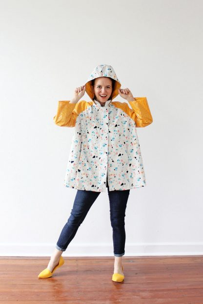 Woman wearing the Whitney Raincoat sewing pattern by Amy Nicole. A raincoat pattern made in waterproof or water resistant fabrics, featuring raglan sleeves, in-seam pockets and a roomy hood.