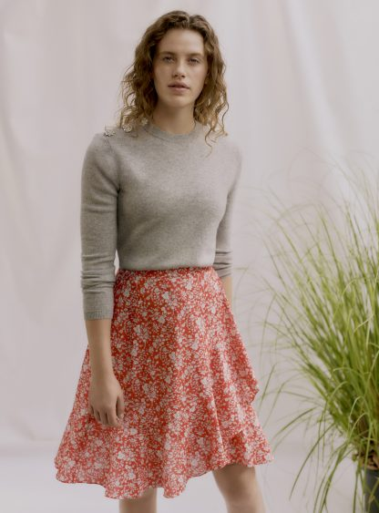 Woman wearing the Zina Wrap Skirt sewing pattern by Liberty Sewing Patterns. A wrap skirt pattern made in lightweight fabrics with drape such as cotton or silk, featuring a left sided self-waist tie and optional gathered tier.