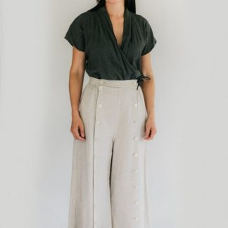 Woman wearing the 231 Big Sky Riding Skirt sewing pattern from Folkwear on The Fold Line. A culottes/skirt pattern made in poplin, denim, gabardine, corduroy, linen, wools or suiting weight silks fabrics, featuring a movable front panel that buttons either to the left, for a skirt effect, or to the right for a trouser effect, side seam pockets and ankle length.