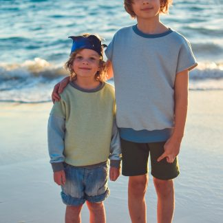 Children wearing the Baby/Child Driftwood Dolman Sweatshirt sewing pattern from Waves and Wild on The Fold Line. A sweatshirt pattern made in medium-weight knit fabric, featuring a relaxed fit, short or long sleeves, round neck and ribbing to the cuff and waist.