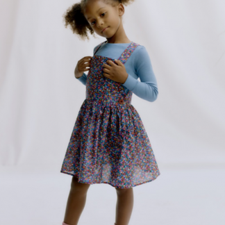 Child wearing the Child/Teen Kiki Dungaree Set sewing pattern by Liberty Sewing Patterns. A pinafore pattern made in denim, corduroy or cotton fabrics, featuring a zip side opening, button fastening straps, flared skirt and knee length finish.
