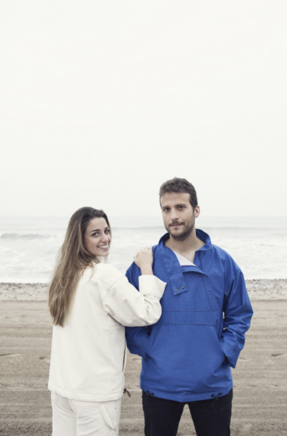 Man and women wearing the Unisex Maritims Pullover sewing pattern by Pauline Alice. A cagoule pattern made in cotton canvas, denim, gabardine, corduroy or nylon fabrics, featuring a large front pocket, high collar with zipped opening, interior pocket, adjustable hem with drawstrings and cuffed sleeves.