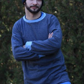 Man wearing the Men's Driftwood Dolman Sweatshirt sewing pattern from Waves and Wild on The Fold Line. A sweatshirt pattern made in medium-weight knit fabric, featuring a relaxed fit, long sleeves, round neck and ribbing to the neck and cuff.