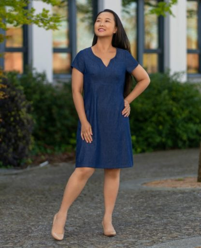 Woman wearing the Recoleta Dress sewing pattern by Itch to Stitch. A dress pattern made in linen's, rayon challis, charmeuse, lawn, chambray, poplin and sateen fabrics, featuring an empire waist, a notched neckline that combines a scoop neck and a V neck, short sleeves and knee length.