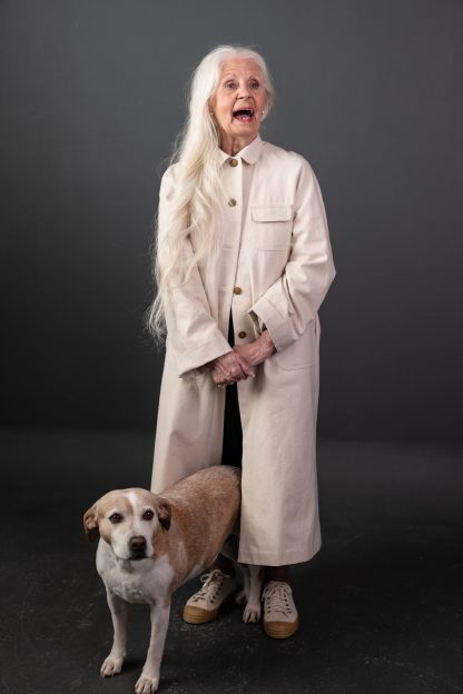 Woman wearing The September Coat sewing pattern from Merchant and Mills on The Fold Line. A duster coat pattern made in dry oilskin, oilskin, mid - heavyweight linens, denim, wool, corduroy, cotton twills or canvas fabric, featuring a relaxed fit, button front closure, breast pocket, midi length, waist pockets and back centre vent.