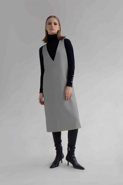 Woman wearing the Stacy Dress sewing pattern by Vikisews. A sleeveless dress pattern made in wool suiting, cotton, tweed, fine coating, gabardine, sturdy velvet, denim or jacquard fabrics, featuring a semi fit, bust darts, in-seam pockets, deep V-neck and below knee length.