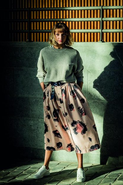 Woman wearing the Alix Skirt sewing pattern from Fibre Mood on The Fold Line. A skirt pattern made in poplin, twill, chambray, corduroy, Tencel, crêpe or satin fabrics, featuring a button front closure, subtle pleating, waistband with belt loops, side seam pockets and mid length finish.