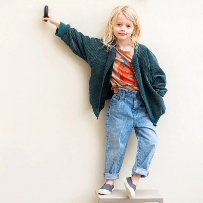 Child wearing the Baby/Child/Teen Cato Bomber Jacket sewing pattern from WISJ on The Fold Line. A jacket pattern made in canvas, oilskin, cotton or softshell, french terry, corduroy or knitted fabrics, featuring raglan sleeves, pockets, long sleeves with ribbed cuffs, front zipper closure and relaxed fit.