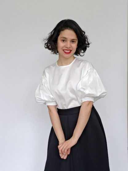 Woman wearing the Cologne Blouse sewing pattern from Bella Loves Patterns on The Fold Line. A blouse pattern made in poplin, chambray, tencel or linen fabrics, featuring a loose fit, dropped shoulders, lantern shaped elbow length sleeves. The sleeves have deep pleats at the top and double elastic cuffs.