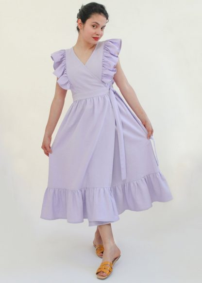 Woman wearing the Flor Dress and Top sewing pattern from Bella Loves Patterns on The Fold Line. A wrap dress pattern made in cotton linen blends, cotton lawns, poplin, voile, broderie anglaise or shirting fabrics, featuring shoulder ruffles, princess seams, wide waist ties, in-seam pockets, gathered waist, tiered skirt and high V-neck.