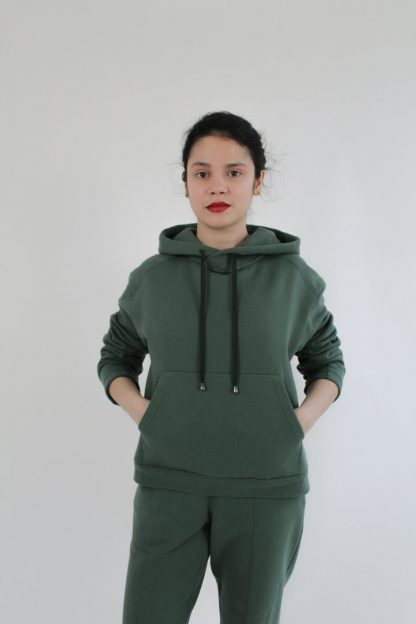 Woman wearing the Interstellar Hoodie sewing pattern from Bella Loves Patterns on The Fold Line. A hoodie pattern made in sweatshirting, French terry, Ponte Roma or cotton fleece fabrics, featuring a moderate oversized fit, angled shoulder yoke, two-piece tapered sleeve, front kangaroo pocket and deep hood.