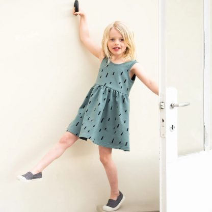 Child wearing the Child/Teen Jente Dress sewing pattern from Itch to Stitch on The Fold Line. A sleeveless dress pattern made in stretch fabrics such as tencel or bamboo jersey, featuring a gathered skirt, overlapping back panels with a low cut and boat neckline.