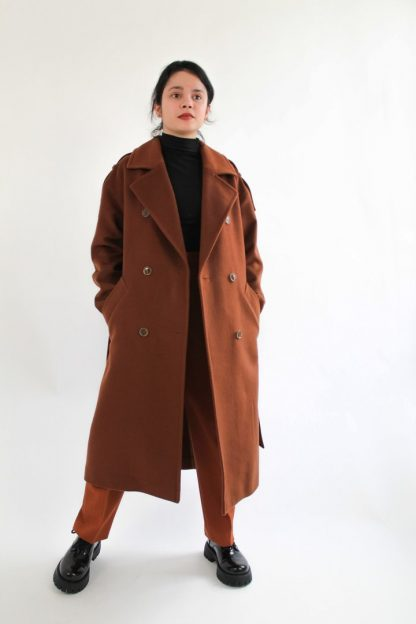 Woman wearing the Traveller Coat sewing pattern from Bella Loves Patterns on The Fold Line. A double breasted coat pattern made in wool, cashmere, boiled wool, Melton, denim, gabardine, or heavier weight linen fabrics, featuring a relaxed fit, mid-calf length, wide notched collar, dropped shoulders, welt pockets and a back vent.