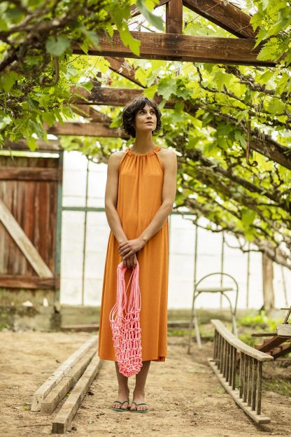 Women wearing the Ulla Dress sewing pattern from Fibre Mood on The Fold Line. A dress pattern made in woven or knit fabrics but with fluid drape, featuring a relaxed fit, calf length, halter neck using a cloth tie and slightly fitting over the bust.